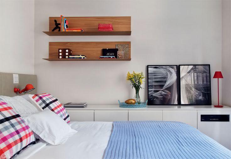 quarto de casal com prateleiras na parede, comoda no chão e quadros decorando