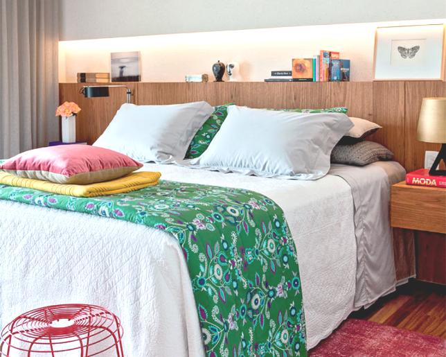 quarto de casal com nicho iluminado na cabeceira, decorado e com estantes suspensas ao lado da cama